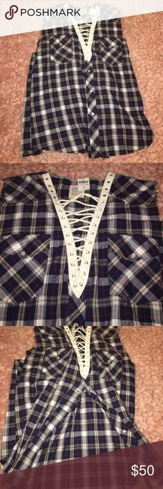 Trendy sleeveless flannel. Can be worn many ways Navy, white, red, & brown flannel. Purchased at LF. One of a kind. Can be tucked into jeans/ jean shorts or tied in the front. White strings at the top can be taken out. Amazing condition Furst Of A Kind Tops