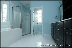 Dark espresso master bathroom cabinets. Powder blue walls. White tile floor, tub surround, and shower.
