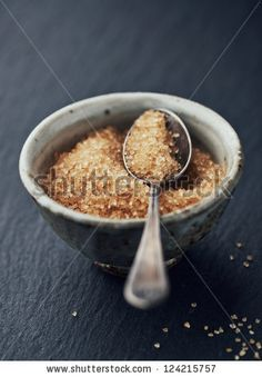 Brown sugar and silver spoon in a ceramic bowl  on dark wood table by B. and E. Dudzinscy, via Shutterstock
