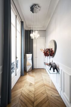 Gorgeous, classic hallway / foyer. Long, dark drapes, wood flooring, chandelier, and white.