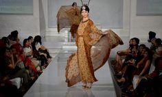 Model mengenakan pakaian batik bergaya ...