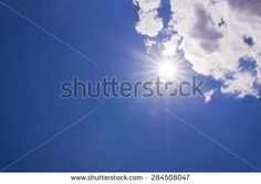 Blurred realistic shining sun with lens flare effect . (Blue sky with clouds)