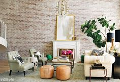 Lauren Conrad's living room with fireplace, fiddle leaf fig tree, and leather ottomans.