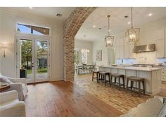 brick arch separating the living room from the kitchen