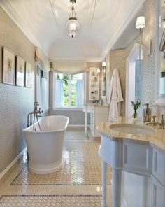 Sometimes you have to work within a limited space. This is a great example of how you can still have an elegant spa style bath in a perhaps less spacious area. Although the bath is not wide, they really took advantage of the length and made a stand alone tub and his and hers vanities work. The light grey and white colors give the space an airy and open feel.