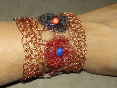 bracelete em croche de fio de metal, cobre esmaltado em dourado, vermelho e azul estes últimos fios importados, bordado com pedra natural, azurita e coral