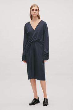 Designed with a twisted drape detail at the front, this dress is made from a heavyweight stretch jersey with a drapey, smooth quality. Coming in gently at the waist, it has wide sleeves, an overlapping V-neck and relaxed shoulders.