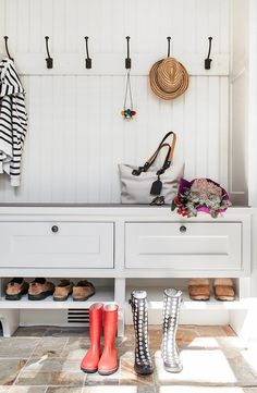 Beautiful mudroom features a built-in bench fitted with drawers and shoe shelves under a row of hooks lining a beadboard wall flanked by floor to ceiling closed mudroom cabinets alongside an orange and gray slate tiled floor.