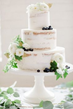A vision in white, this nearly naked cake was the work of local pâtissier Jenny Williamson. Wreathed with eucalyptus, it was scantily clad in clusters of English ivy, 'Majolica' spray roses, sweet peas, camellias, ranunculi, and sprigs of spirea. A scattering of blueberries added a pop of contrast. | Photo by Deborah Zoe