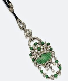 DIAMOND, JADE AND PEARL PENDANT, CARTIER, CIRCA 1915 Designed as a flower-filled basket supporting a flexible garland of leaves and berries, composed of a carved jade plaque and jade beads, small pearls and numerous single-cut diamonds, mounted in platinum, signed Cartier, supported on a black cord necklace with platinum and rose-cut diamond pendant loop and fittings
