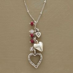 HEART TRIO NECKLACE--A heart pendant and gemstone necklace, with three heart charms, each distinct, representing love in its various forms. A sprinkling of garnet and rose quartz is a romantic touch. Handcrafted exclusive in sterling silver