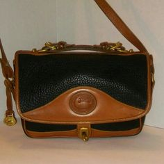 Dooney & Bourke Vintage  AWL Crossbody/Satchel Classic style in a Black ,(navy?)pebbled AWL leather cross body/satchel. Trimmed in tan leather, featuring adjustable buckle handle, cross body strap, flap with turn lock clasp, pocket to interior and cloth label with no. C226451.  Purchased from a private estate sale, this piece has been lovingly cared for.   Black felt interior is spotless.  Exterior shows signs of age ( handles are soft,/hardware on flap is a little loose) but no dirt or…