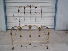 vintage old antique cast iron bed with fancy decorative clusters in original paint