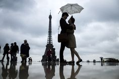 People gather on the Trocadero Square in front of the Eiffel Tower on a rainy day on May 20 in Paris