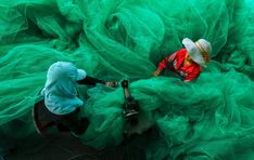 Smithsonian Magazine Grand Prize Winner. Women of a small village near Vinh Hy Bay, Vietnam, sew a fishing net while their husbands fish. Vinh Hy bay, Ninh Thuan, Vietnam. Photographed by Pham Ty from Vietnam.