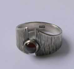 Textured and oxidised silver ring withgarnet cabochon in rub over setting