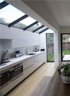 Living this all white modern kitchen with overhead natural light