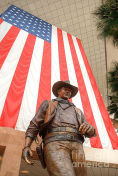 """John Wayne Airport is an international airport in an unincorporated area in Orange County, Calif. Originally named Orange County Airport, the county Board of Supervisors renamed it in 1979 to honor the actor John Wayne, who resided in neighboring Newport Beach and died that year. After the renaming, the John Wayne Associates commissioned sculptor Robert Summers to create a bronze statue of """"the Duke."""" The 9 foot statue was dedicated to the County on Nov. 4, 1982. Photo by Deborah Smolinske"""