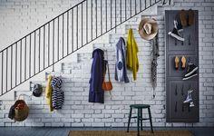 Ganchos para colgar abrigos y chaquetas en la pared de debajo de la escalera. Frente de puerta colgado en la pared, con ganchos para los zapatos.
