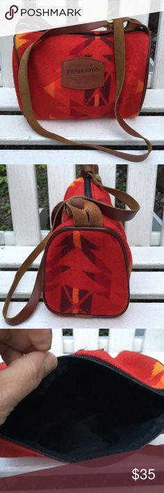 Pendleton wool crossbody bag small duffle tribal Red crossbody bag made out of red blanket wool and tan leather.  Very simple and timeless with the Western Native  American Feel.  Lined with black nylon.  Shows some wear on the corners you can see a bit of the white loom threads. (See last photo).  The white threads don't take away from the beauty of the purse.  In good used condition.  I believe it's 1990's item Pendleton Bags Crossbody Bags