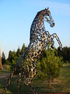 """'Gabriel' - a life-sized horse statue made with 630 recycled horseshoes that stands almost 11 feet tall - sculpted by Bud Thomas of Oregon Horseshoe Art;  """"Even the detail in the mane, tail, face and each hoof are made by heating and shaping the horseshoes.  When finished, the artist ground all the welds smooth and then sandblasted the entire piece. He was then heat treated using a torch and buffed out. Finally [he was] powder-coated with a glossy black finish."""""""