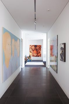 The third-floor hallway art gallery leads to guest bedrooms and bathrooms