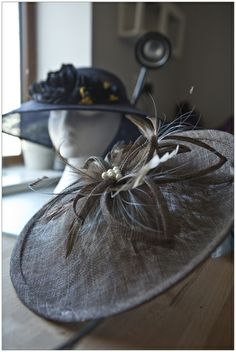 Tobacco saucer hat with sinamay flower and pearl centre - in the background, hand blocked nay hat with handmade navy taffetta roses. x