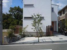 植栽に囲まれた、コンクリートのシンプルナチュラル駐車場(箕面市)1