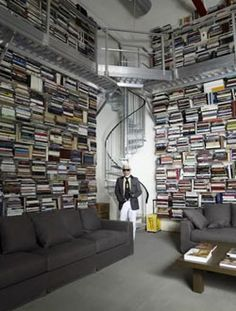 Karl Lagerfeld's very large home library in his photo studio apartment in Central Paris. He had 60,000 books, mostly concerning fashion and art, making it one of the world's largest private libraries. His bookshelves appear to be made of thin steel, running the length of each wall of the large room, and about three stories up. A steel circular staircase ascends to the steel catwalk that encircles the space about fifteen feet off the floor, and a steel platform ladder on wheels allows access…