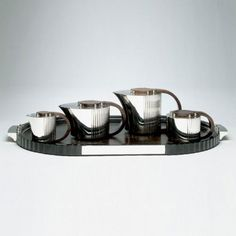 Art Deco: This 1930's Jean Puiforcat silver-plated coffee & tea set has fashionable streamlined half-reeded bodies with contrasting hardwood covers.