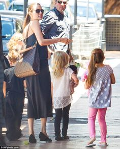 Walking advertisement: The mother-of-six was once the face of Louis Vuitton, and carried one of the designer's signature handbags over her s...