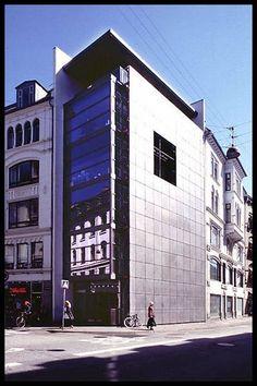 På et centralt københavnsk gadehjørne har et stort bladhus fået nyt indgangsparti plus 5 mindre kontorafsnit. Mod vest markerer huset sig med perforerede stålplader og et mørkt hul, der skal symbolisere redaktørens kontor.