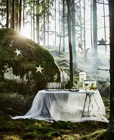 A table for mingle drinks at a forest wedding with a lace-like curtain tablecloth and hanging star decorations