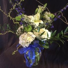 Hydrangeas, lilies, delphinium, daisy  and curly willow. Blues and whites go wonderful together.