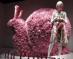 printemps windows in paris 2011 paper roses painted pink on the oversized snail ... would be more interesting adding teen dolls or a miniature setting near the snail to contrast with the mannequin's size