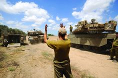 An Israeli soldier directs a Merkava tank at an army deployment area near Israel's border with the Gaza Strip, on Thursday.