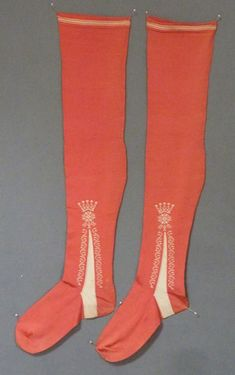 Men's coral silk stockings, 1725-1750. Frame knitted, both sides woven with cream clocks surmounted by a five balled crown, above flower and foliage meanders flanking the cream foot inserts, the top woven with a wide band flanked by two narrower bands.