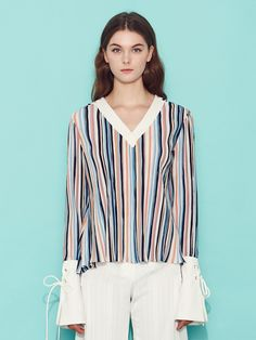 0ac1a7bddfeffe Striped V-neck blouse with exaggerated flared eyelet cuffs.Color  .