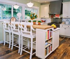 A beautiful spring green accent on the walls provides a perfect splash of color in this eclectic, vintage single line kitchen with white cabinets & beautiful butcher block breakfast bar.