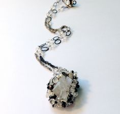 I love the combination of a big raw crystal surrounded by more refined gems. This one has black and white tourmaline, some almondine garnet and white topaz and chain mixed in as well. 17 inch patchwork twisted chain. The pendant is 1.5 inches long and it is finished with a silver box clasp with a white CZ. $210.00