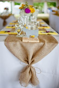 White linen, tied burlap, flowers, favors, holder for napkins/silverware? maybe silver instead of burlap??