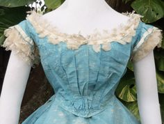 Ball Gown C 1865 | eBay Blue silk taffeta trimmed w/white satin, tulle & lace. Satin trim around neckline studded w/glass fish scale pearls. Gathered bodice &pleated skirt. Piped at armholes. Bodice hem bound w/self fabric.