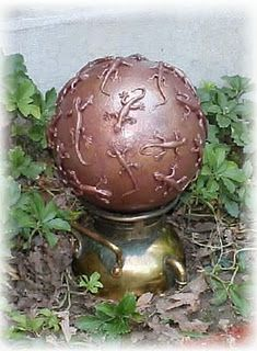 Plastic toys glued to a surface and painted. Interesting idea for a garden orb.