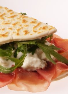 PIADINA ROMAGNOLA ~~~ piadina aka piada is the flatbread used in this famous italian sandwich; the filling construct consists of prosciutto, taleggio cheese, and arugula. recipe gateway: this post's link has recipes for both the bread and sandwich AND here are a couple more recipes for the bread, itself at http://food52.com/recipes/4251-nonna-s-piadina AND http://www.ricette-bimby.com/2010/07/piadina-romagnola-col-bimby.html [Italy, Emilia-Romagna] [saveur] [food52]