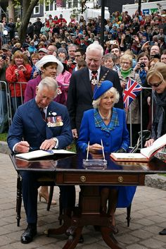 The Prince of Wales and The Duchess of Cornwall sign a welcome book at the Grand Parade in Halifax. 19th May 2014