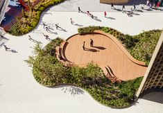 Aerial photograph of a plaza consisting of white tiled floors and a curving platform made from brick and corresponding planters surrounding it. Landscape Plaza, Landscape Architecture Design, Urban Landscape, Urban Architecture, Classical Architecture, School Architecture, Ancient Architecture, Sustainable Architecture, Landscaping Supplies