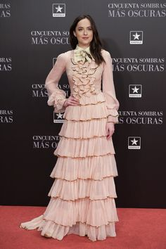 """To the """"Fifty Shades Darker"""" premiere in Madrid last night, Dakota Johnson wore a Gucci Pre-fall 2017 chiffon ruffled gown with gold sequin trimming, tiered skirt and silk floral brooch, designed by Alessandro Michele."""