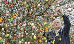 Volker Kraft decorates a tree with thousands of Easter eggs in his garden in Saalfeld, Germany. (Jens Meyer/Associated Press)