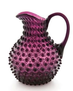 Fenton Hobnail Purple Pitcher.  Hobnail glassware gets its name from the studs, or round projections, on the surface of the glass. These studs were thought to resemble the impressions made by hobnails, a type of large-headed nail used in bootmaking.  Fenton Art Glass introduced Hobnail Glass in translucent colors in 1939 & Milk Glass Hobnail in 1950