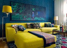 Sala con un llamativo color de pared que contrasta con el sofá amarillo.